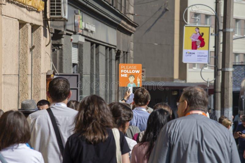 Turist- grupp samman med handboken, som håller affischen Please för att följa mig som promenerar gatan i Lviv, Ukraina royaltyfri fotografi