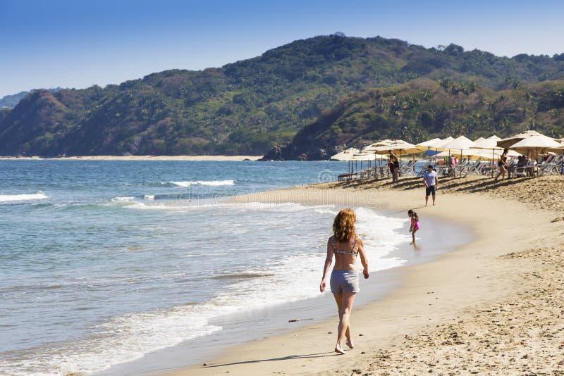 Turist- ha en morgon att gå vid den Sayulita stranden i Mexico royaltyfria bilder