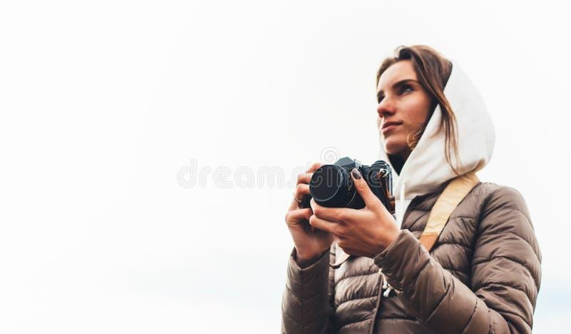 Turist- handelsresande för yrkesmässig fotograf som står på på ett vitt bakgrundsinnehav i digital fotokamera för händer, fotvand royaltyfri bild