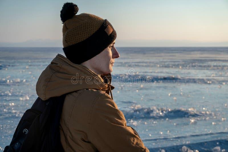 Turist- handelsresande med en ryggsäck som håller ögonen på solnedgången på den snöig isen av Lake Baikal begrepp av frihet och l royaltyfria foton
