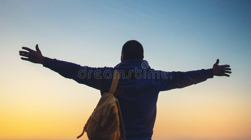 Turist- handelsresande med ryggsäckanseende med lyftta händer, fotvandrare som ser på solnedgång till dalen i tur, ung man för hi royaltyfria foton