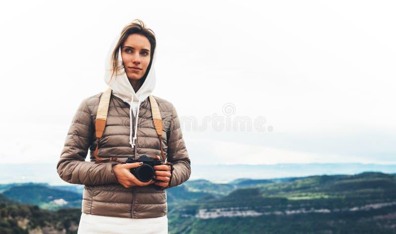Turist- handelsresandeanseende för fotograf på gräsplanöverkant på berginnehav i den digitala fotokameran för händer, fotvandrare arkivfoton