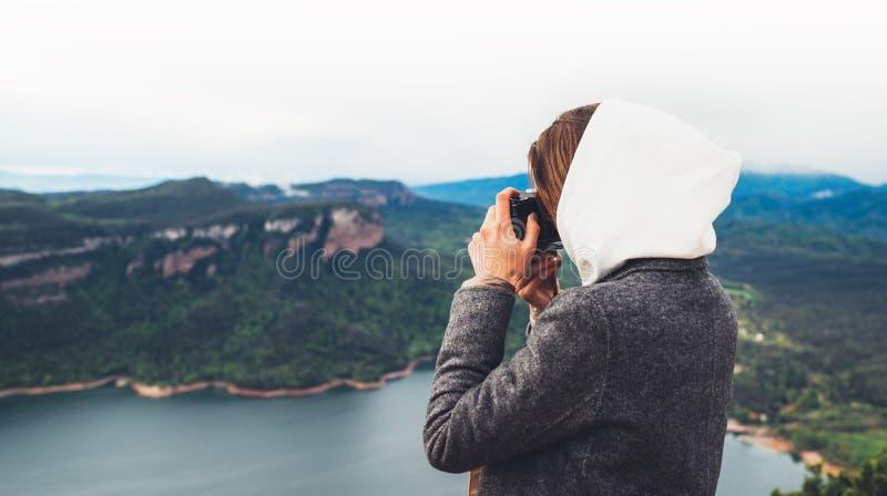 Turist- handelsresandeanseende för fotograf på gräsplanöverkant på berginnehavet i digital fotokamera för händer, fotvandraresikt royaltyfri foto