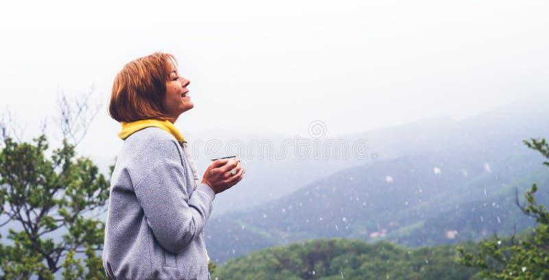 Turist- handelsresandeanseende på gräsplanöverkant på berget, ung flicka som ler och rymmer koppen med den varma drinken mot en b royaltyfri fotografi