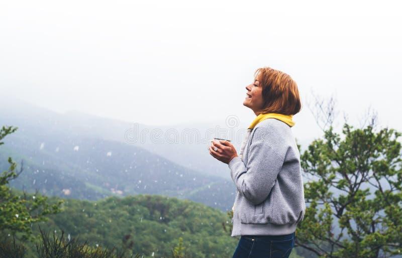Turist- handelsresandeanseende på grön överkant på berget, ung flicka som ler och rymmer koppen med den varma drinken mot en bakg arkivfoton