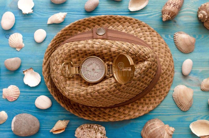 Turist- hatt, kompass, snäckskal och kiselstenar fotografering för bildbyråer
