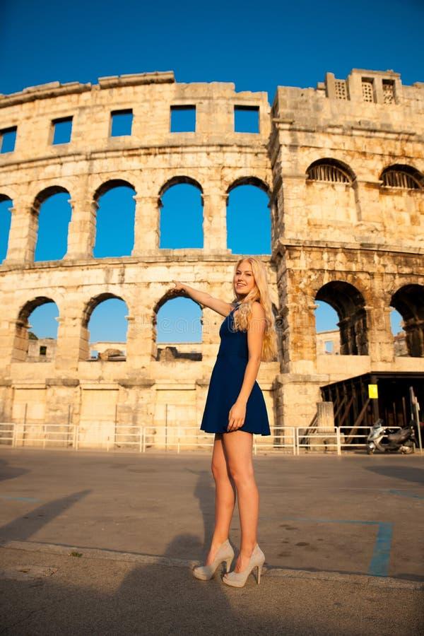 Turist hermoso de la mujer joven que toma las fotos de la arena romana en Pul imágenes de archivo libres de regalías