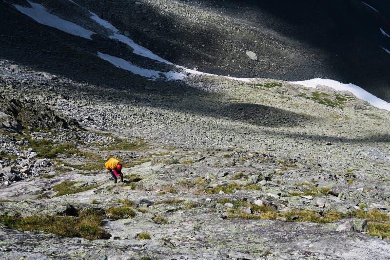 Turist- klättrar upp stenarna i bergen Gå upp den steniga morän royaltyfri fotografi
