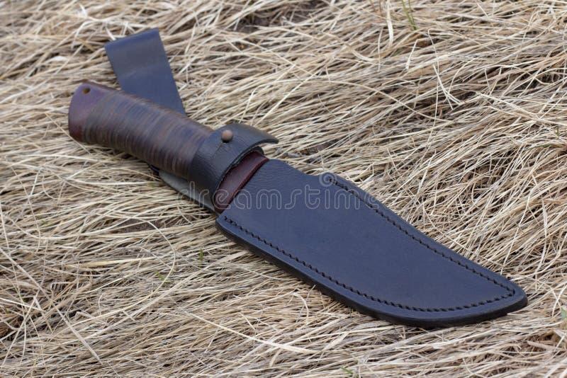 Turist- kniv på torrt gräs, jaktkniv som dödar, royaltyfria bilder