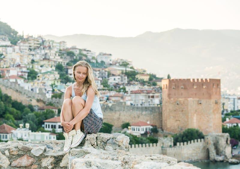 Turist- koppla av för ung blond kvinna på den forntida fästningväggen av den Alanya slotten Kizil Kule eller rött torn på bakgrun arkivbild