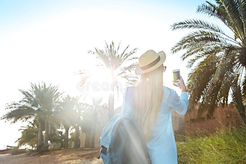 Turist- kvinna i hatten som tar fotoet av den gamla delen av Dubai att använda arkivfoto