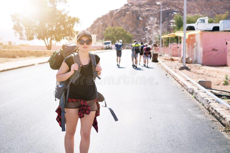 Turist- kvinna med vänner i en öken Den naturliga Jordanien parkerar Wadi Rum Fotvandrare på vägen Kvinnafotvandrare med ryggsäck arkivbild