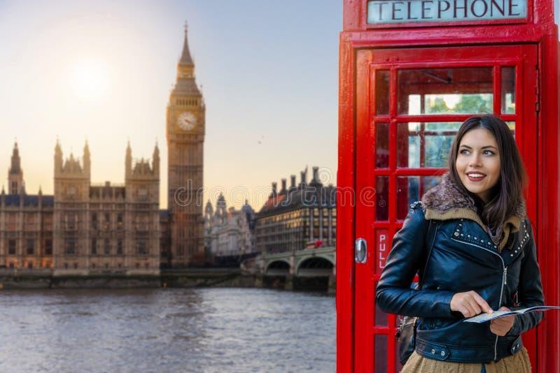 Turist- kvinna på ett rött telefonbås framme av det Big Ben tornet royaltyfria foton