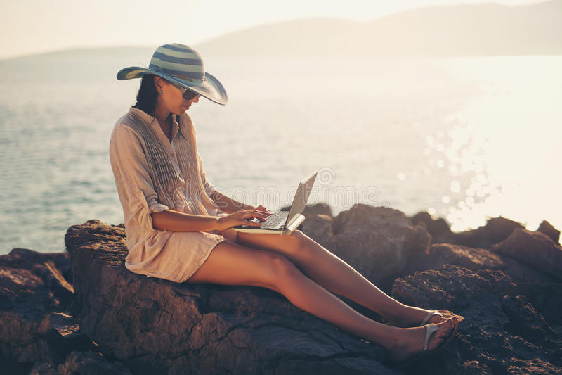 Turist- kvinna på ferier som direktanslutet tycker om med en bärbar dator på stranden royaltyfria bilder