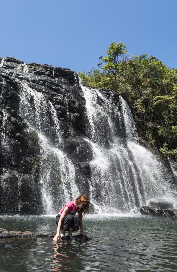 Turist- kvinna som sitter nära den enorma härliga vattenfallet royaltyfri foto