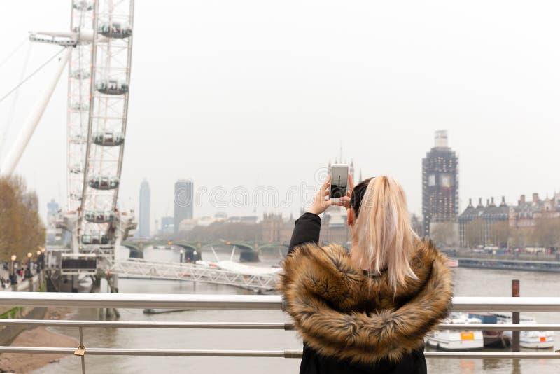 Turist- kvinna som tar bilden av London Eye med mobiltelefonen vid Thames River arkivbild