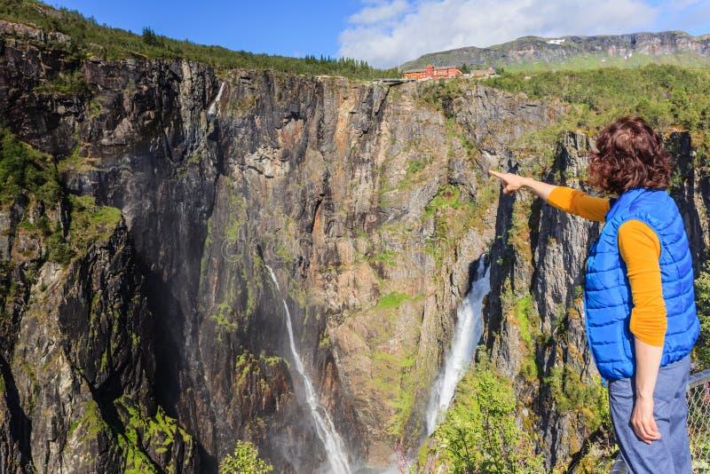Turist- kvinna vid den Voringsfossen vattenfallet, Norge royaltyfri foto