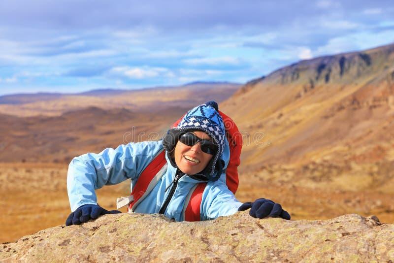 Turist- kvinnaklättring på ett berg arkivbild