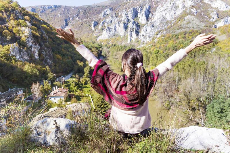 Turist- kvinnasammanträde på överkanten av höstberget som tycker om sikten arkivbilder