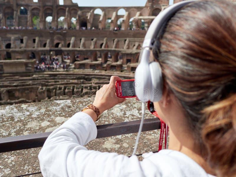 Turist- kvinnor lyssnar audioguiden, medan besöka Colosseumen royaltyfri bild