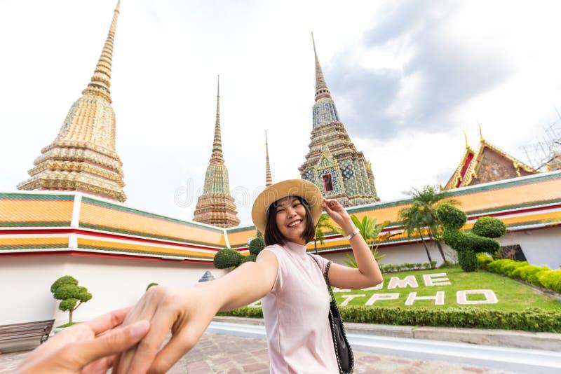Turist- kvinnor med den ledande mannen för hatt som reser i den Wat Pho templet royaltyfri foto