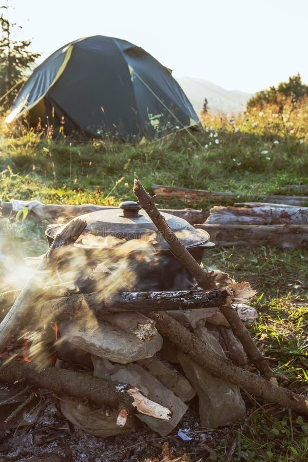 Turist- läger med brand, krukan, tältet och vedträ arkivbilder