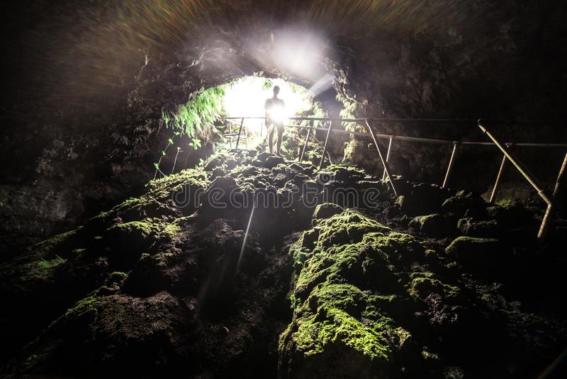 Turist- man att undersöka lavagrottan med pråligt ljus i Maui, Hawaii arkivbilder