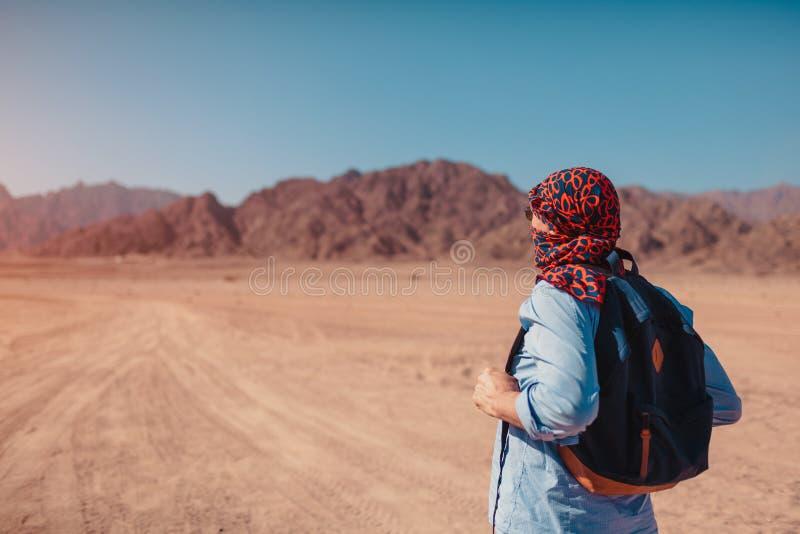 Turist- man med den bärande halsduken för ryggsäck på huvudet Lycklig handelsresande som beundrar den Sinai öknen och berg royaltyfri fotografi