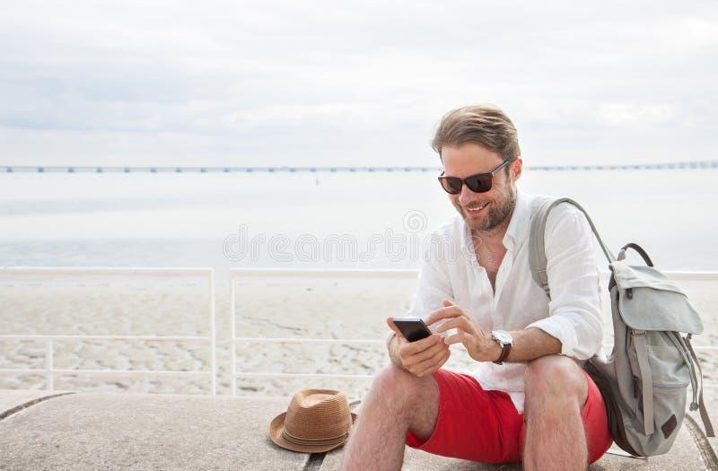 Turist- man med ryggsäcken som ser mobiltelefonen som är utomhus- vid havet royaltyfri foto