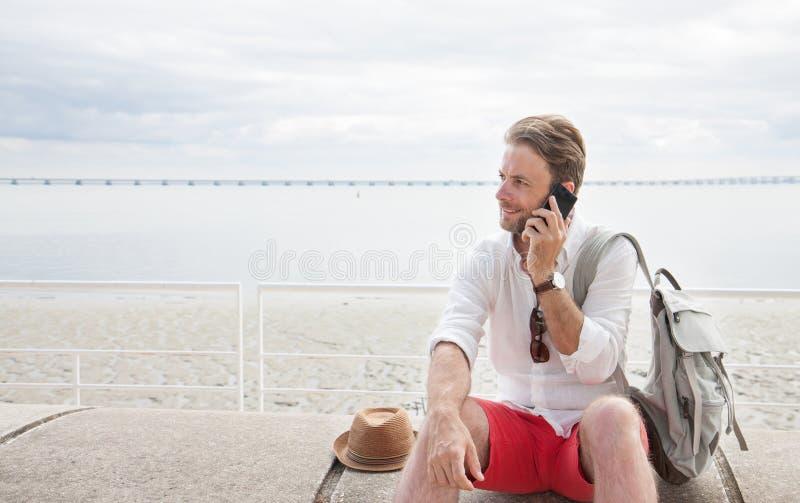 Turist- man med ryggsäcken som talar på en mobiltelefon vid havet royaltyfri bild