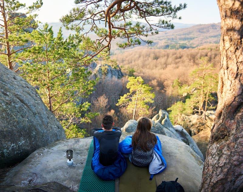 Turist- man- och flickasammanträde i sovsäckar på det stora berget vaggar royaltyfri bild