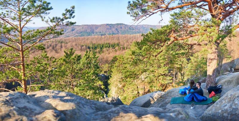 Turist- man- och flickasammanträde i sovsäckar på det stora berget vaggar royaltyfri foto