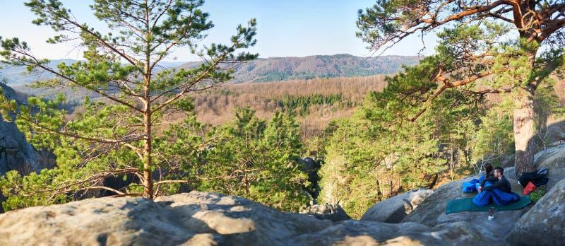 Turist- man- och flickasammanträde i sovsäckar på det stora berget vaggar arkivbilder