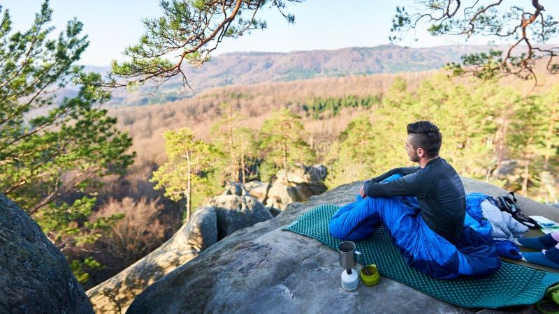 Turist- man- och flickasammanträde i sovsäckar på det stora berget vaggar arkivfoto
