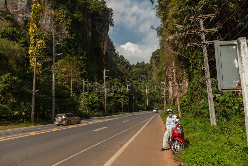 Turist- mansammanträde på den klassiska sparkcykeln mot bakgrunden av bergen av det Krabi landskapet, Thailand arkivfoto