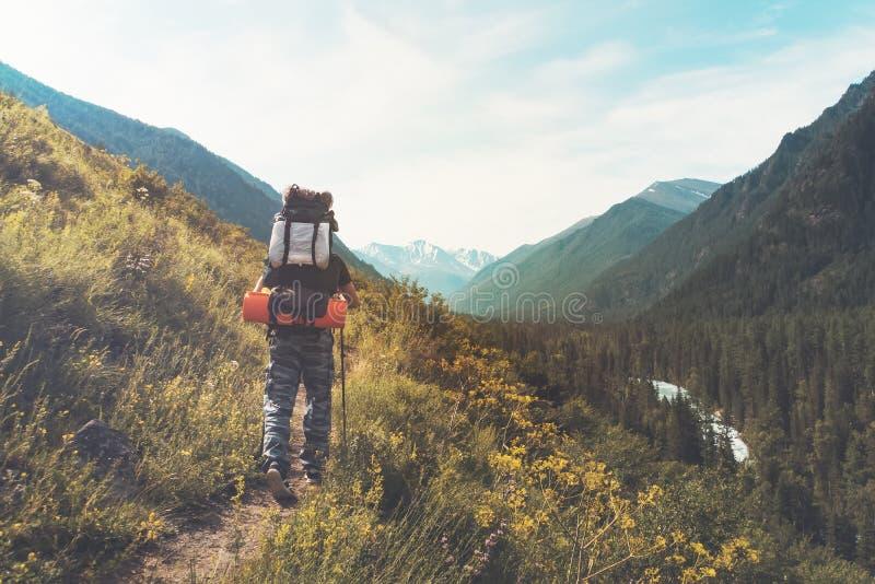 Turist med att fotvandra ryggsäckar i bergvandring på sommardag Turist i härligt berglandskap Den unga grabben går vidare foten royaltyfria foton