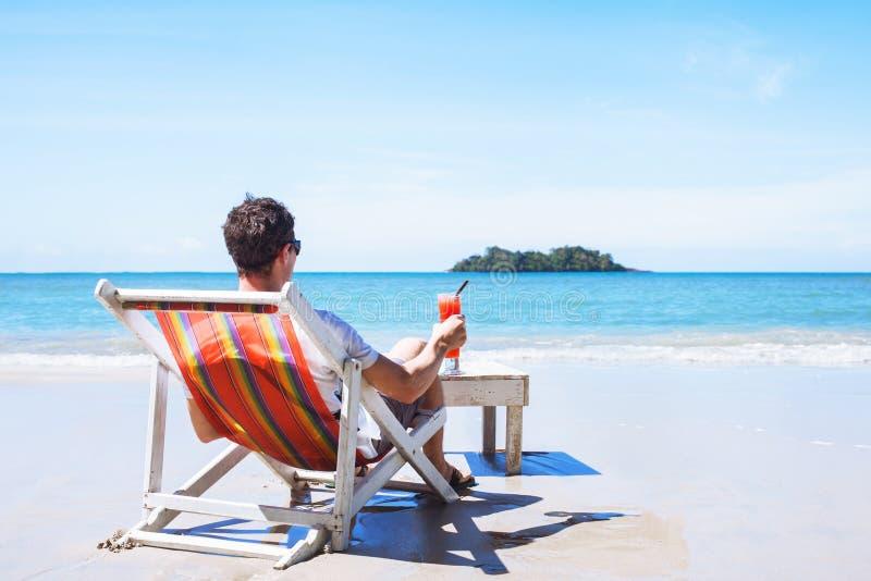 Turist med coctailen på stranden royaltyfri foto