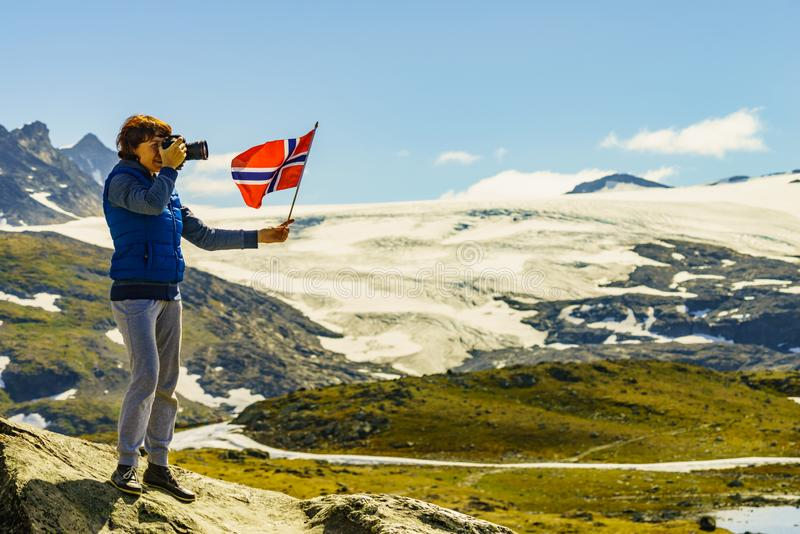 Turist med kameran och flagga i Norge berg royaltyfri fotografi
