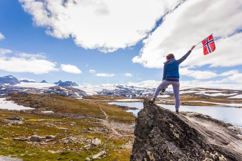 Turist med kameran och flagga i Norge berg royaltyfri bild