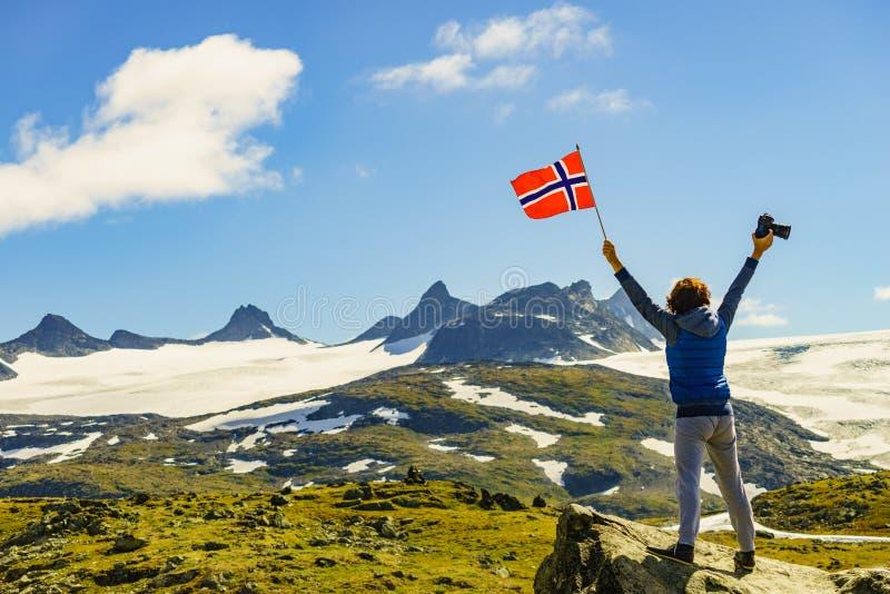 Turist med kameran och flagga i Norge berg arkivbilder