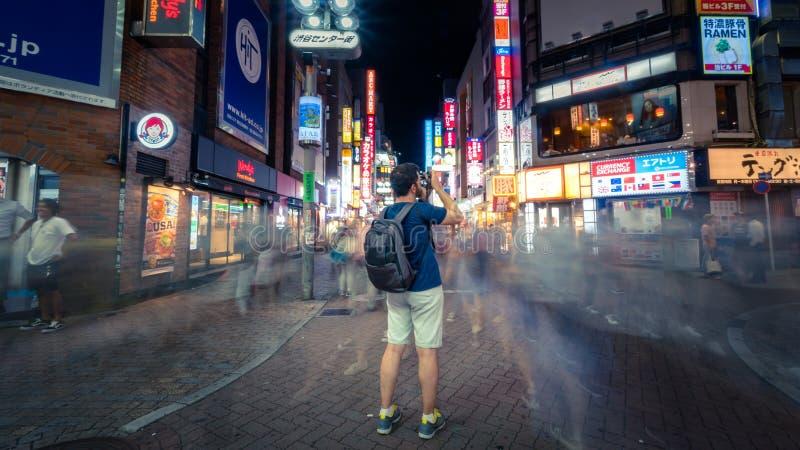 Turist med kameran som fortfarande står i Shibuya som shoppar området med oidentifierade suddiga gångare i Tokyo, Japan arkivbild