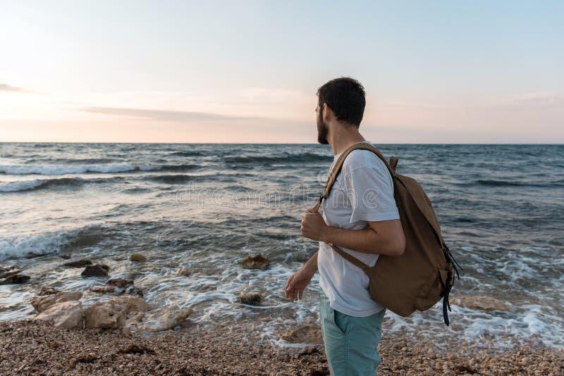 Turist med ryggsäckanseende på bakgrunden av havet fotografering för bildbyråer