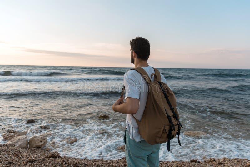 Turist med ryggsäcken som håller ögonen på solnedgången över havet arkivbild