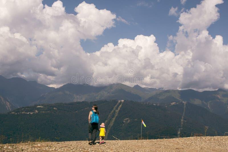 Turist- moder och dotter som går i bergsikterna swallowtail för sommar för fjärilsdaggräs solig Horisontal föreställa arkivfoto