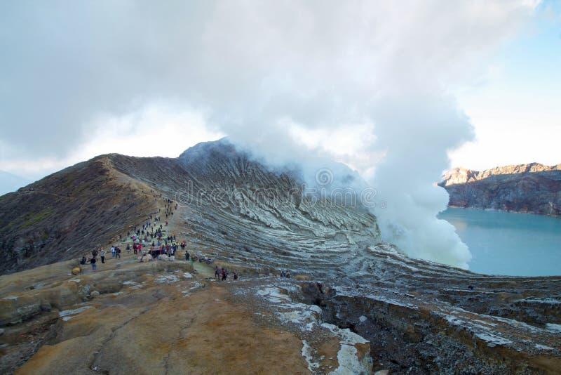 Turist- near arbetare som bär svavelstycken från vulkan arkivbild