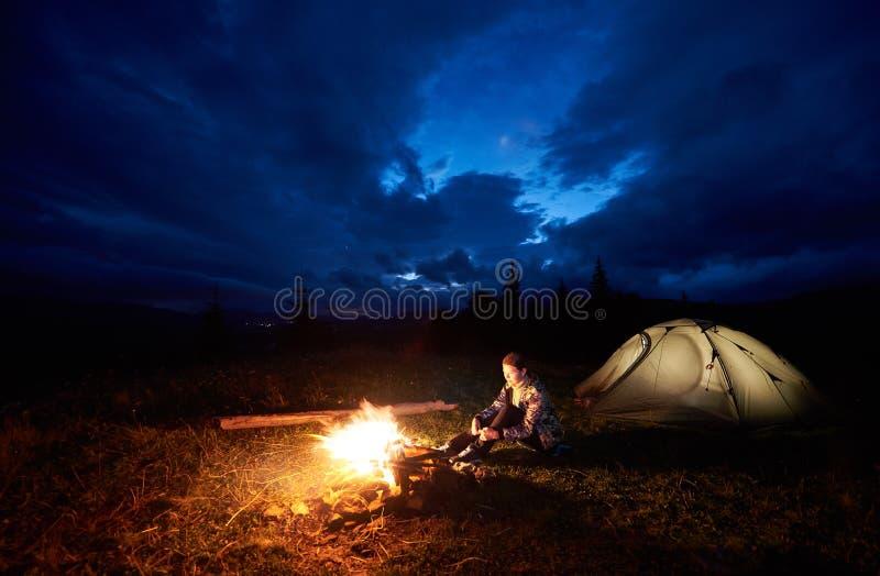 Turist- near vila för kvinna på natten som campar i berg, lägereld och tältet under molnig himmel för aftonen arkivfoton