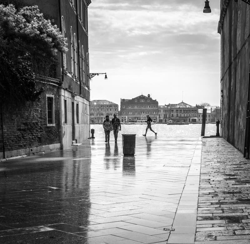 Turist och lokalfolk som går vid den venetian gatan efter hällregnet i Venedig, Italien arkivfoto