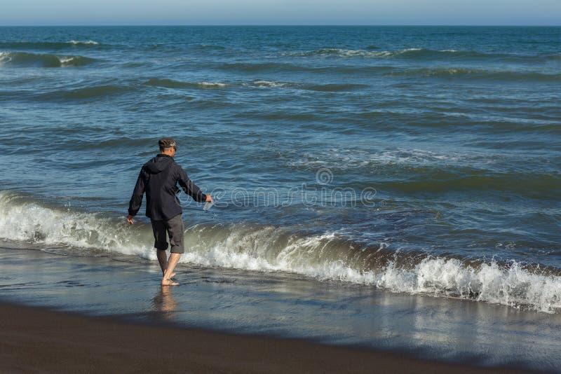 Turist på den Khalaktyrsky stranden med svart sand Stilla havet tvättar den Kamchatka halvön arkivfoto