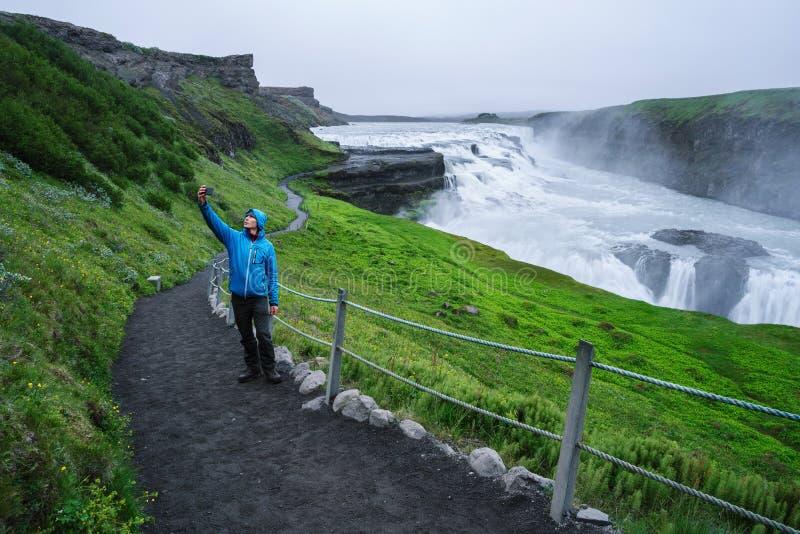Turist på en tur nära den Gullfoss vattenfallet i Island arkivbild
