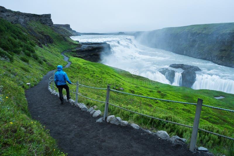 Turist på en tur nära den Gullfoss vattenfallet i Island royaltyfri fotografi